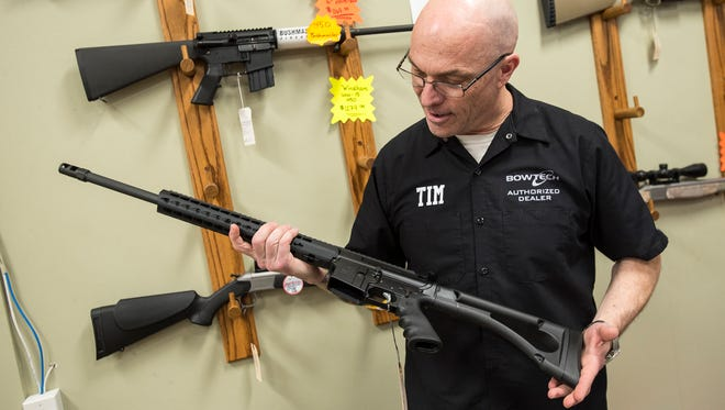 Store owner Tim Daniels holds a 450 Bushmaster rifle inside The Hock Shop and Sporting Center in Port Huron, Michigan, Feb. 28. The rifle looks like an AR-15 rifle, but it shoots a straight-walled pistol cartridge and is legal in zone three hunting areas.