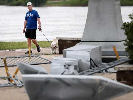 Bob Bernstein from Birmingham, Alabama walks by the downed Tom Lee memorial in Tom Lee Park Sunday morning after a severe thunderstorm knocked out power to most of Memphis Saturday night.