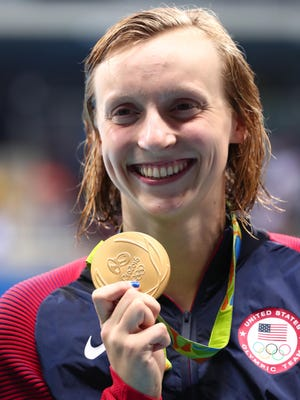 Katie Ledecky holds her gold medal from the women's 200m freestyle on Tuesday.