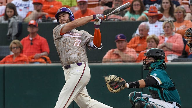 Clemson senior infielder Chris Williams(27) hits a fly ball against Coastal Carolina during the bottom of the sixth inning on Tuesday at Doug Kingsmore Stadium in Clemson.
