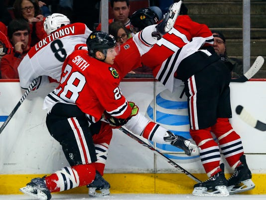 Carolina Hurricanes center Andrei Loktionov (8) is checked into the boards by Chicago Blackhawks left wing Jeremy Morin (11) and right wing Ben Smith (28) during the second period of an NHL hockey game in Chicago, Friday, March 21, 2014. (AP Photo/Jeff Haynes)