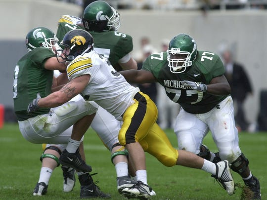 Iowa's Matt Roth gets through the Spartan offensive line and sacks quarterback Jeff Smoker. MSU offensive lineman Steve Stewart can only watch.
