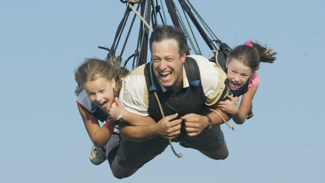 Eric Fehrenbach of Marshfield, hangs on to his daughters Ellie, 7, left, and Emalee, 5, as they fly from the top of the bungee ride at the Central Wisconsin State Fair in September.
