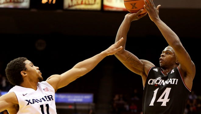 Cincinnati guard Ge'Lawn Guyn shoots against Xavier University guard Dee Davis on Dec. 14, 2013.