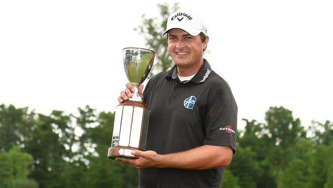 Brian Stuard holds the Zurich Classic winner's trophy.
