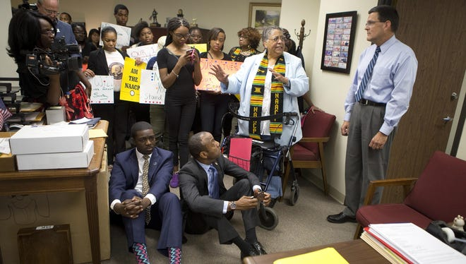NAACP national youth and college director Stephen Green, seated left, and NAACP national president Cornell William Brooks, seated right, sit down first to demonstrate a sit-in at U.S. Rep. Bob Goodlatte's regional office as Goodlatte's chief of staff Pete Larkin, right, listens to local NAACP president Brenda Hale explain why they are there, Monday, Aug. 8, 2016, in Roanoke, Va. Brooks and Green were charged with trespassing and refusing to sign a summons at the end of a six-hour sit-in at Goodlatte's district office in downtown Roanoke to call attention to changes to the Voting Rights Act. (Erica Yoon/The Roanoke Times via AP)