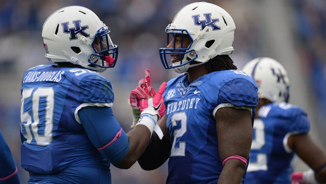 """UK DE Alvin """"Bud"""" Dupree celebrates with DT Mike Douglas during the first half of the University of Kentucky Wildcats Football game against Louisiana-Monroe in Lexington, KY. Saturday, October 11, 2014."""