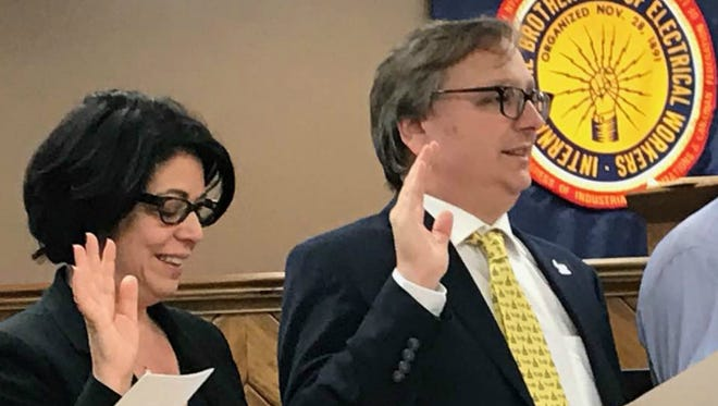 Leonard Assante, right, takes the oath of office as a member of the Democratic State Executive Committee in Nashville, Tenn. Mary Mancini, left, takes the oath as party chairwoman.