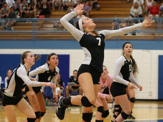 Jumping off the floor to reach the volleyball Tuesday night is Plymouth's Keara Warner (No. 7).