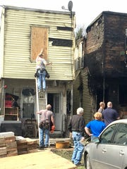 As contractors work to board up windows, victims of Wednesday night's fire commiserate in the backyard of a three-unit row house in the 700 block of North Seventh Street in Lebanon that was destroyed by fire Wednesday night.