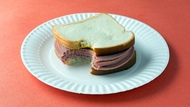 A classic bologna sandwich with mustard and white bread.