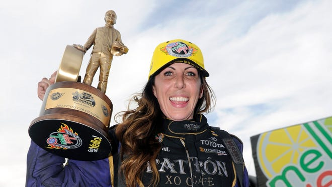 In this photo submitted by the NHRA, Alexis DeJoria celebrates her first career NHRA drag race for the Funny Car victory, Sunday, Feb. 23, 2014, in Chandler, Ariz. She is the 14th female driver to win an NHRA Mello Yello Series race and the fourth to do it in Funny Car.