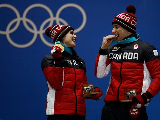 Gold medalists in the ice dance, free dance figure skating Tessa Virtue and Scott Moir, of Canada, celebrate during their medals ceremony at the 2018 Winter Olympics in Pyeongchang, South Korea, Tuesday, Feb. 20, 2018. (AP Photo/Charlie Riedel)