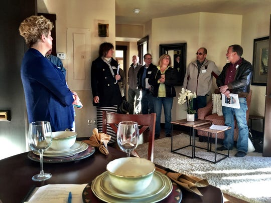 Realtor Beth Schoenen, second from left, shows developers, real estate brokers and city officials one of the Montana Building condos during the recent walking tour showcasing downtown development successes and buildings that still need work.