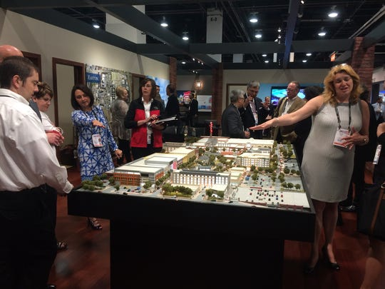 Attendees at the International Council of Shopping Centers RECon conference gather around the model of Steiner & Associates' Liberty Center project Monday, May 18, 2015.