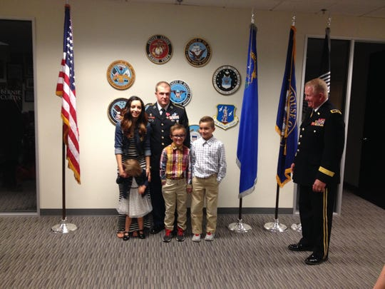 Sgt. Jon Wright, center, with is wife Chelsea and children Charley, Jax and Jonny with Brigadeer General Todd A Plimpton, right, at a ceremony presenting Wright with the Bronze Star with V device for valor.