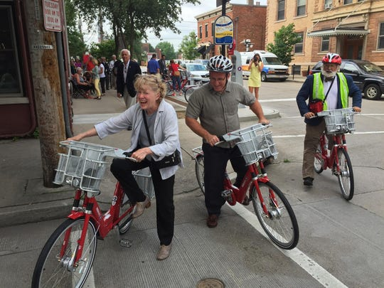 Covington Mayor Sherry Carran (left) laughs as she gingerly gets on a Red Bike while Roebling Point bookstore owner Richard Hunt (second from left) and Queen City Bike president and Red Bike board member Frank Henson look on.