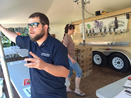 Anello Mollica, owner of Central Waters Brewing Company, operates a stand during the Midwest Renewable Energy Association's Energy Fair last week in Custer. The Amherst beer company recently unveiled two new beers, Summarillo and HGH APA.