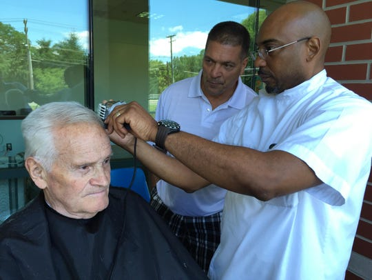 Anthony Barton cuts Joe Kilgallen's hair while student Gino Morasco looks on at Greenburgh Town Hall in 2015. Barton has taught barber skills to ex-convicts, troubled youths and career changers.