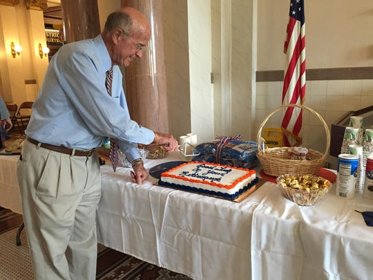 District Judge Kenneth Neill cuts the cake at his retirement party at the Cascade County Courthouse on Monday. The judge retires this week after 19 years on the bench.