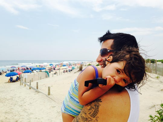 Fifteen-month-old Valentina Pestaner rests her head on the shoulder of her father, Josh, at Assateague State Park on Friday.
