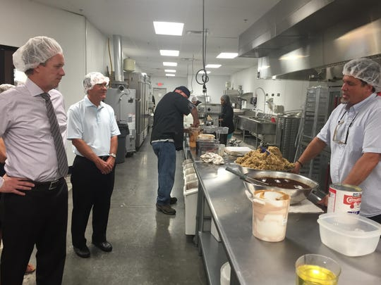 Mayor Greg Fischer eyes a batch of handcrafted cookie dough and hot fudge while Comfy Cow founder Tim McGee leads a tour of the company's new Jeffersontown plant. July 21, 2015.