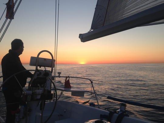 John Cooke takes a turn at the wheel as the sun peeks over the horizon.