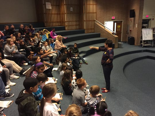 Children's book author Chrysa Smith (standing) talks to fourth graders at Millville's Holly Heights School on Friday. The topic was descriptive writing.