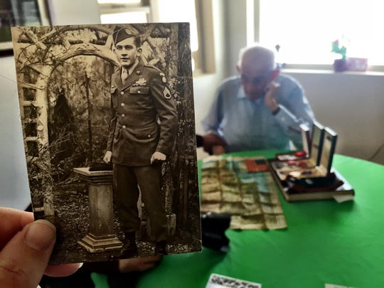 Bud Olson looks through photos and mementos from World War II.