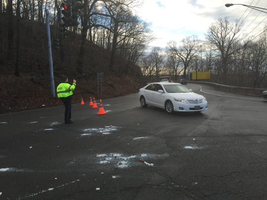 A Rockland County sheriff's officer directs traffic off Route 9W toward New City on Thursday, Feb. 25, 2016. The heavy winds overnight knocked down utility poles and wires forcing the closure of Route 9W into Haverstraw.