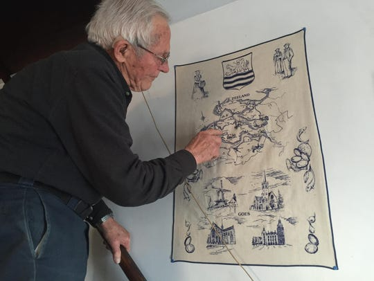 John Wisse uses a tea cloth map to show where his hometown