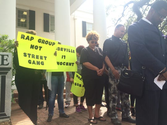 Friends and family members of the supposed 'Gremlins Gang' hold signs behind Rev. Brown and Barnett as they speak to the media about the group.