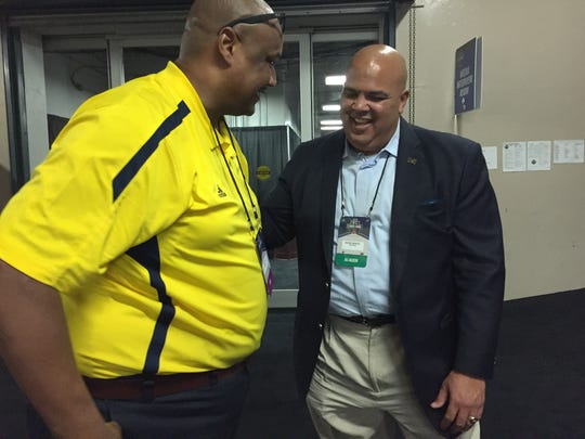 Michigan AD Warde Manuel, right, catches up with Michigan basketball radio analyst Terry Mills before the Wolverines' NCAA tournament game in 2016 in Dayton, Ohio. Both were student athletes at U-M in the 1980s.