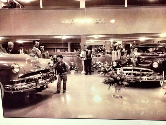 This historic photo shows a reception at Bennett Motors to show off the new car models.