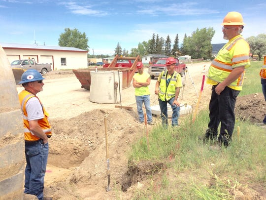 Chris Rider, a state worker with the Montana Department of Transportation, right, talks with Robert Ragland, left, of Schellinger Construction about installing a storm drain in White Sulphur Springs.