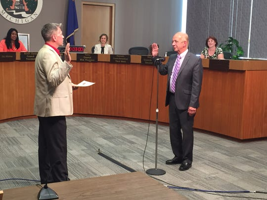 In a file photo, City Clerk Chris Swope, left, swears-in Jim Smiertka as Lansing's city attorney on June 27, 2016.