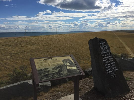 The large grassing area is the Fort Peck Dam, with Fort Peck Lake behind it. A sign at this location tells of the day in 1938 the dam gave way during construction, killing eight workers, including six buried in the dam.