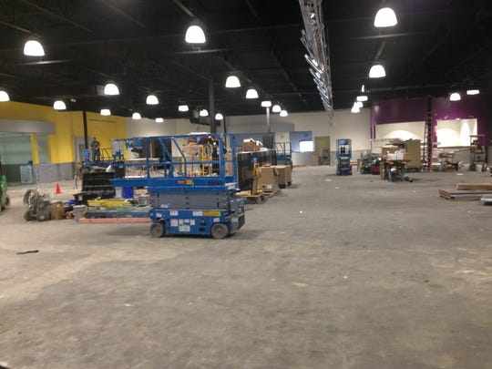 Workers on Tuesday prepare the interior of  a Planet Fitness center in Delhi Township for the addition of more than $2.3 million in exercise equipment and other amenities.