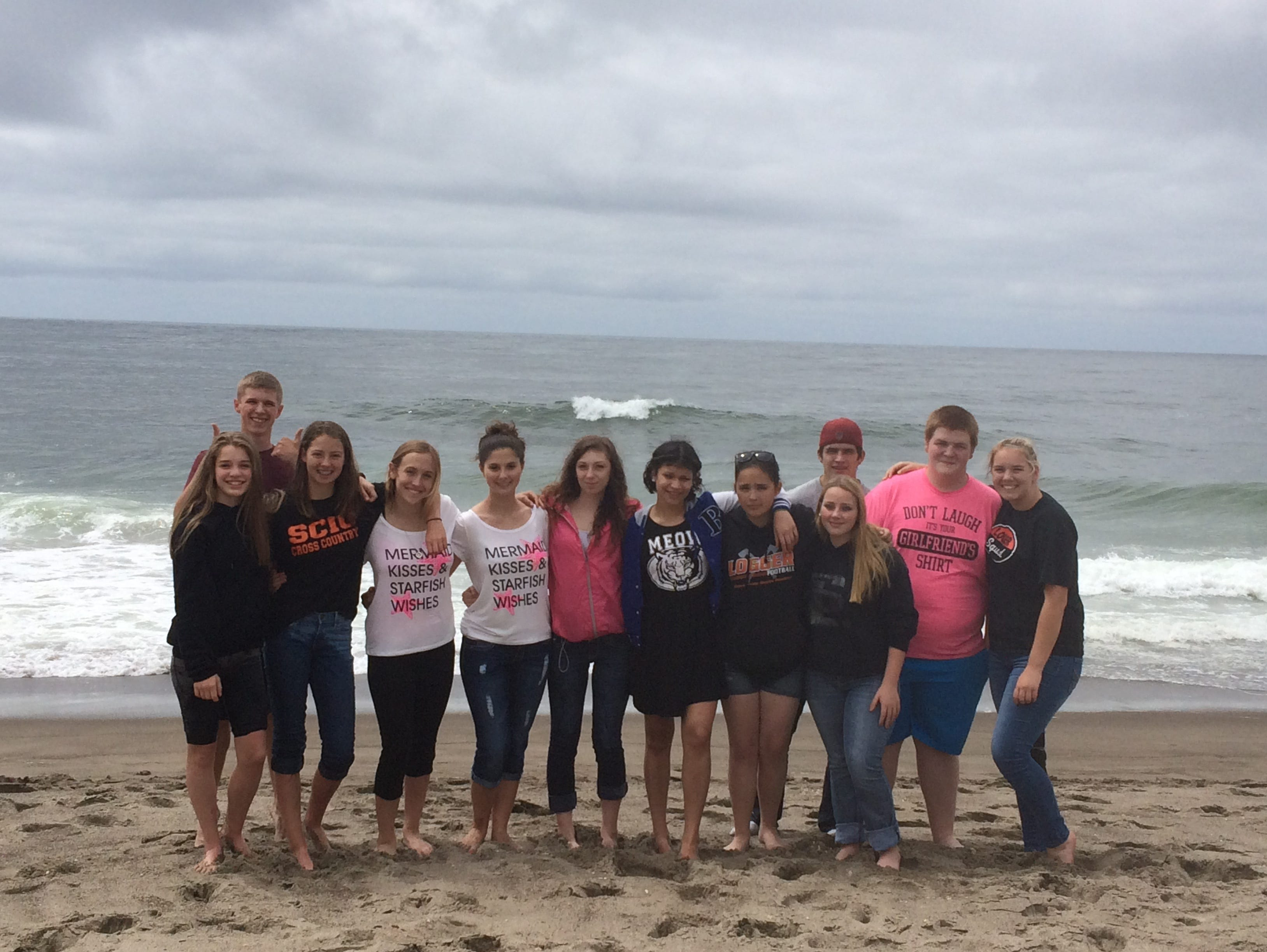 Members of the Scio High School cheer team take a team-building beach timeout (from left: Emilie Pastega, Stephen Cate, Macy Bodine, Ashley Mask, Shyanne Hysell, Chloe James, Anna Hart, Shannon Campos, Zak Mance, Megan Evans, mascot Ethan Olson, and Valerie Clouse.