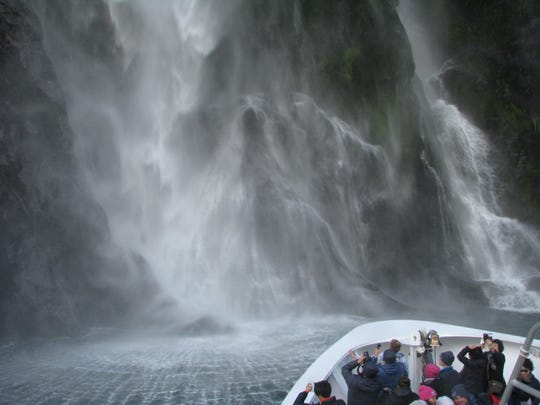 Visitors admire a waterfall during a cruise of Milford