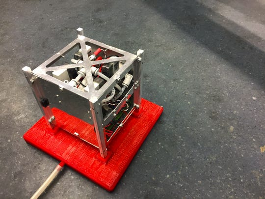 A test bed developed by GreenScale Technologies at UVM simulates space by suspending a small satellite on a cushion of air pumped into the red platform created through 3D printing.
