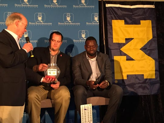Former Michigan football player Jareth Glanda draws a raffle ticket at Wednesday's ninth annual Big Game Tablegate media luncheon. Former Wolverine Mario Ojemudia, right, also attended the event in Southfield.