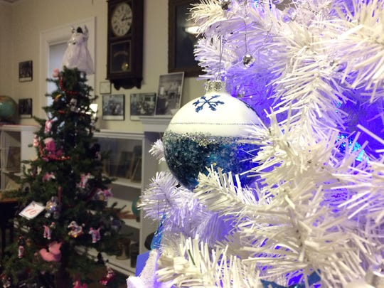 """A """"Blue Christmas"""" tree display stands next to """"Oodles & Oodles of Labs & Poodles"""" at the South Wood County Historical Museum in Wisconsin Rapids."""