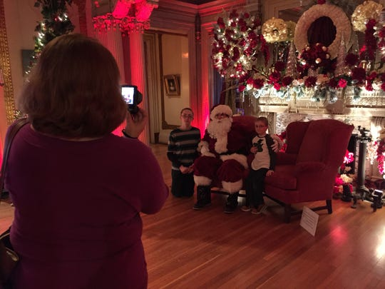 Nicholas Zetzsche, 13, and Zachary Zetzsche, 6, both of Vestal, pose with Santa Claus during Roberson Museum and Science Center's Home for the Holidays on Sunday.