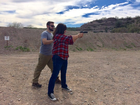 Virgil Bland instructs Karina Bland in firing a pistol