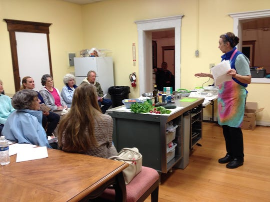 From left to right, Denise Victorine (back to camera), Marlyne Priester (back to camera), Carol Bauer, Amelia Saunders, Kay Thhornburg, Nancy Sbragia, Patrick Marchese, Jim Charlton and his dog Fiasca (in the shadowed doorway) and Chef Cynthia Kroon discuss healthy eating on a budget at a free cooking class sponsored by Healthy Communities Coalition on Feb. 20.
