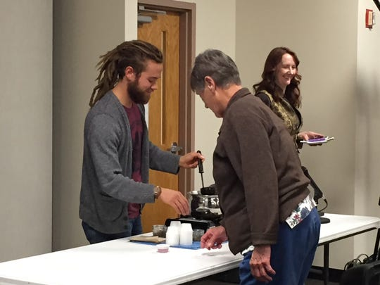 Nicholas Copley of Lionheart Medicinal Gardens serves out samples of an herbal tea he has just made, at the 7th Annual Raising Richland Community Garden Summit at Longview Center Thursday.