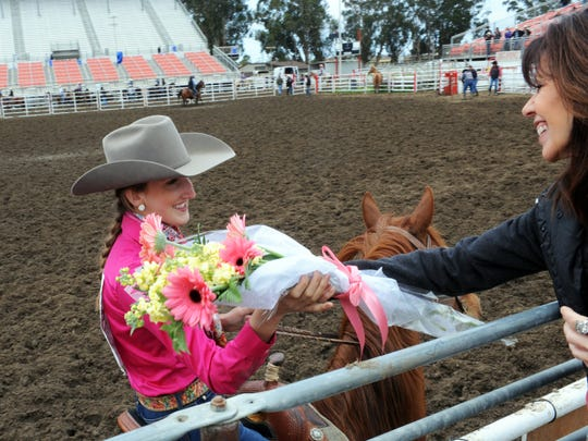 District 6 Queen Sheridan Knight gets a bouquet of flowers from Kari Van Blarcom at the California High School Rodeo competition on Sunday at the Salinas Sports Complex.