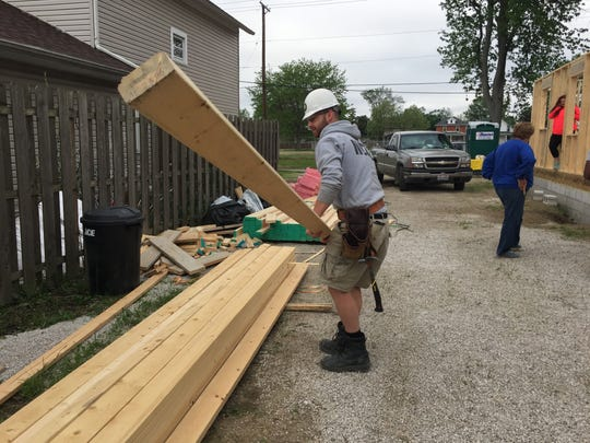 Curtis Willard, 23, of Maine, prepares wood to be cut while building a home at 151 Buchanan St. for Habitat for Humanity.