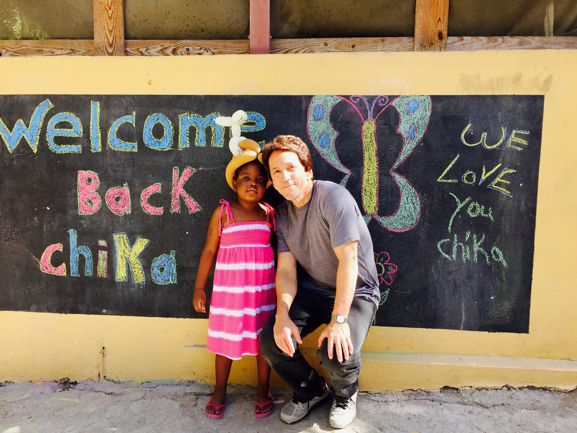 "For the first time since leaving for treatment, Chika returned to Haiti in December 2015. Her arrival was triumphant. The kids painted a welcome mural and when the SUV pulled up, chanted ""Chi-ka! Chi-ka!"""